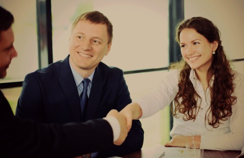 Young woman with long hair, shakes hands with a man in an business meeting, Representing a Pay4 meeting