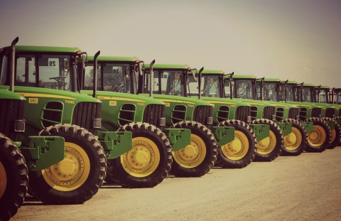 New green tractors in a row - representing the manufacturing industry that Pay4 has as a customer base