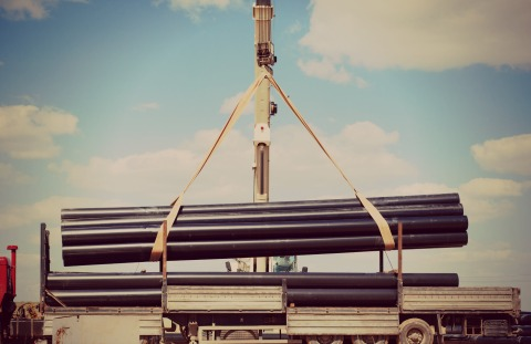 Long black pipes being lifted by crane onto a truck