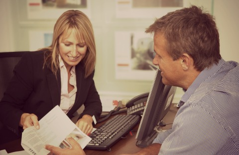 Smiling woman presenting a document, to a man at an office desk. Representing Pay4 business